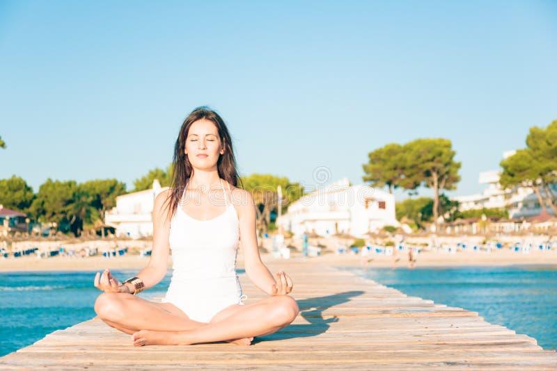 Mujer joven que hace yoga en el embarcadero imágenes de archivo libres de regalías