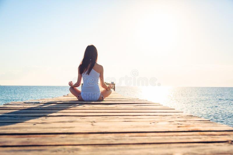 Mujer joven que hace yoga en el embarcadero foto de archivo