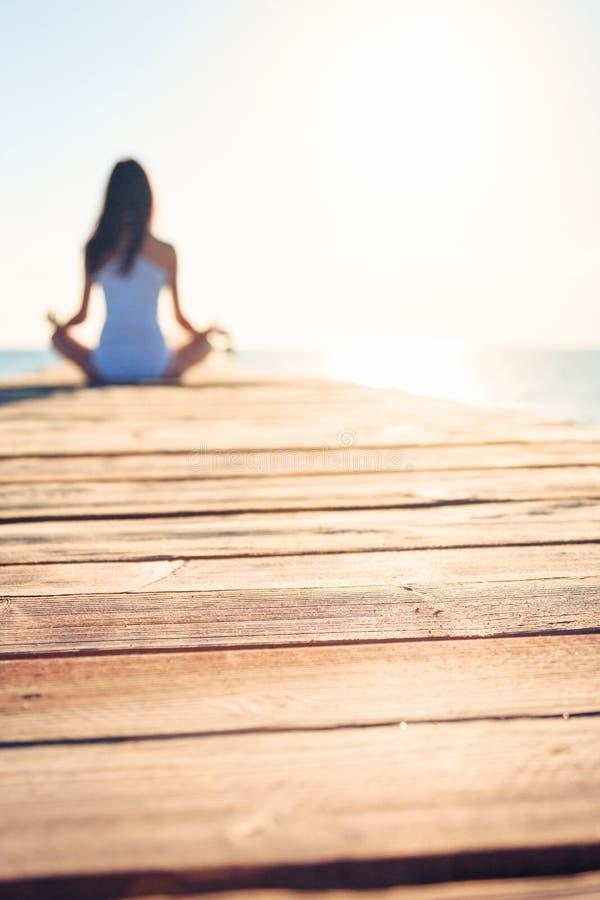 Mujer joven que hace yoga en el embarcadero fotos de archivo libres de regalías
