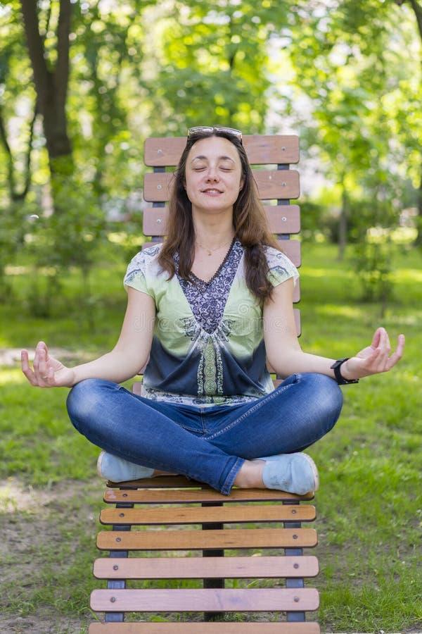 Mujer joven que hace yoga en el parque en el banco Retrato de la mujer morena joven hermosa tranquila que relaja y que hace ejerc imágenes de archivo libres de regalías