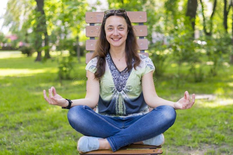 Mujer joven que hace yoga en el parque en el banco Retrato de la mujer morena joven hermosa tranquila que relaja y que hace ejerc fotos de archivo libres de regalías