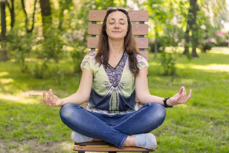 Mujer joven que hace yoga en el parque en el banco Retrato de la mujer morena joven hermosa tranquila que relaja y que hace ejerc foto de archivo