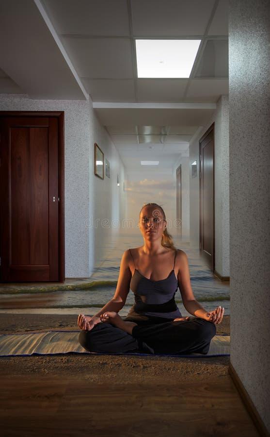 Mujer joven que hace yoga en la oficina, la arena y las ondas en el piso y las nubes en el cielo fotos de archivo