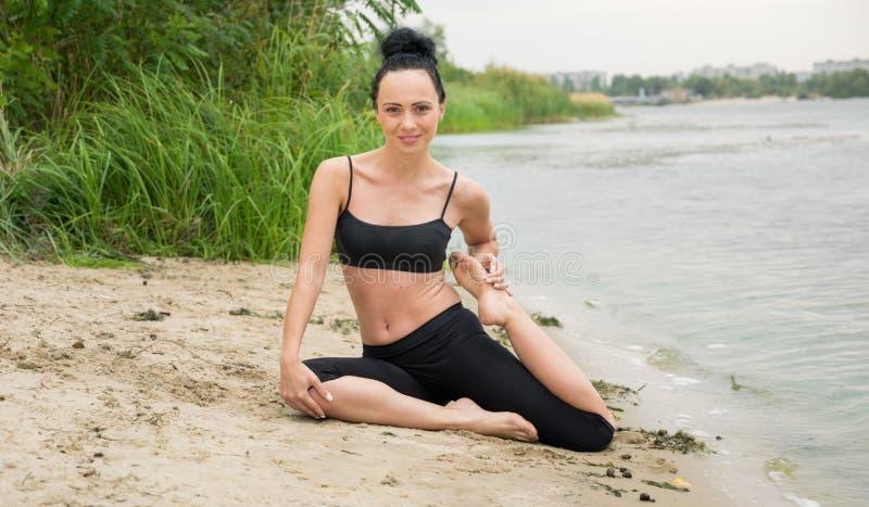 Mujer joven que hace yoga en la orilla del río Rotura de ciudad fotos de archivo