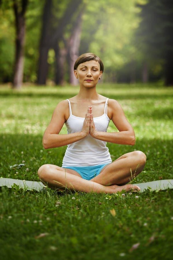 Mujer joven que hace yoga por la mañana en el parque imagen de archivo
