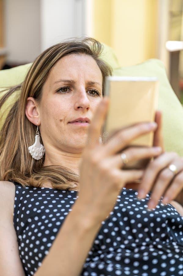 Mujer joven que hojea en su teléfono celular fotos de archivo libres de regalías