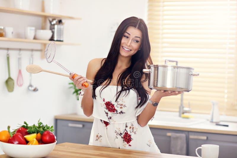 Mujer joven que intenta cocinar algo en cocina fotos de archivo