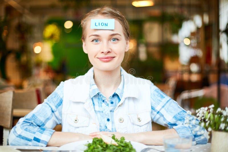 Mujer joven que juega al juego con los amigos en restaurante imagen de archivo