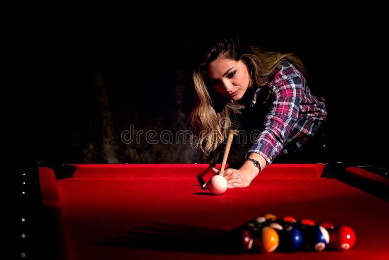Mujer joven que juega billares en el club oscuro del billar imagen de archivo