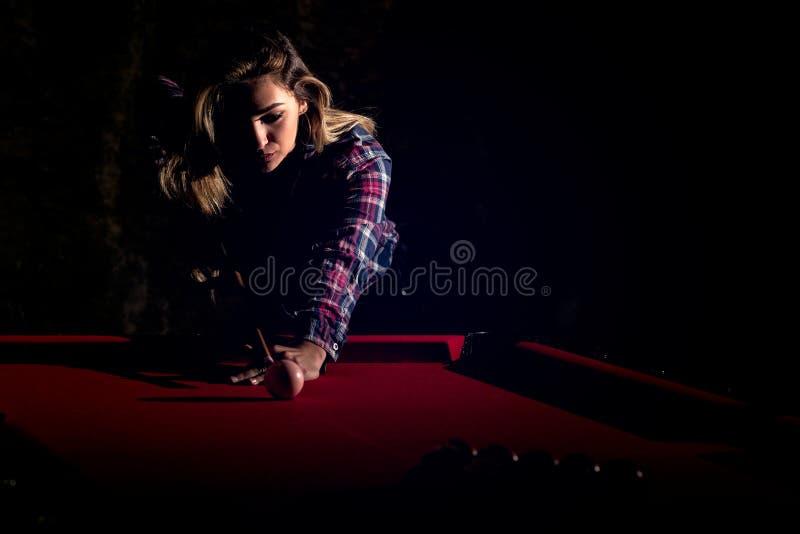 Mujer joven que juega billares en el club oscuro del billar fotos de archivo