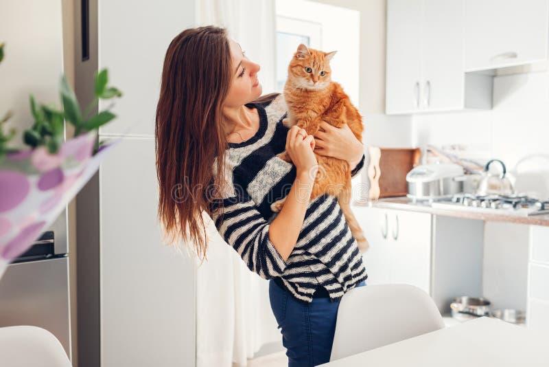 Mujer joven que juega con el gato en cocina en casa Muchacha que sostiene y que abraza el gato del jengibre fotografía de archivo