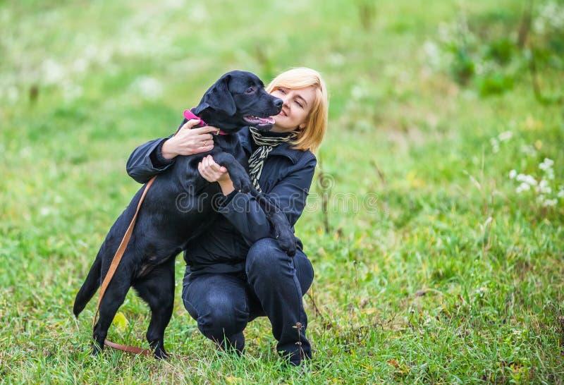 Mujer joven que juega con el perro foto de archivo