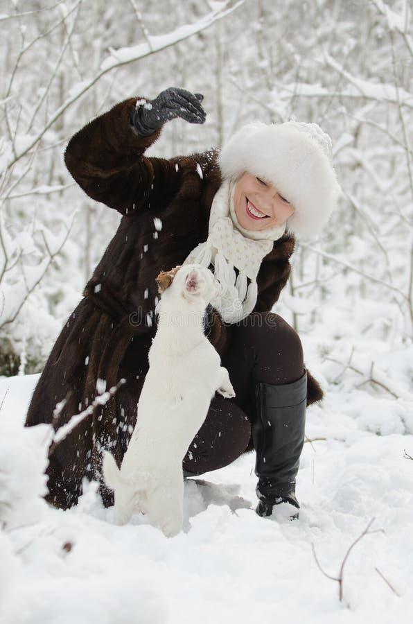 Mujer joven que juega con el terrier de Jack Russell imágenes de archivo libres de regalías