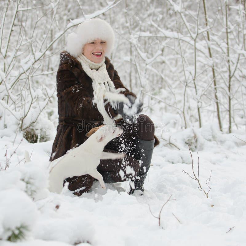 Mujer joven que juega con el terrier de Jack Russell foto de archivo libre de regalías