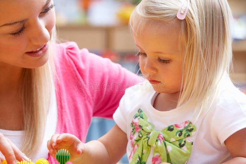 Mujer joven que juega con la muchacha imagen de archivo