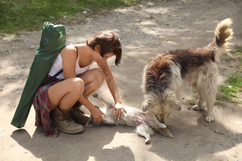 Mujer joven que juega con los perros perdidos al aire libre foto de archivo
