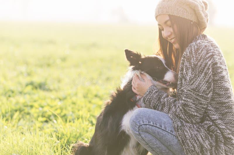 Mujer joven que juega con su perro del border collie fotografía de archivo
