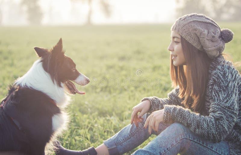 Mujer joven que juega con su perro del border collie fotos de archivo