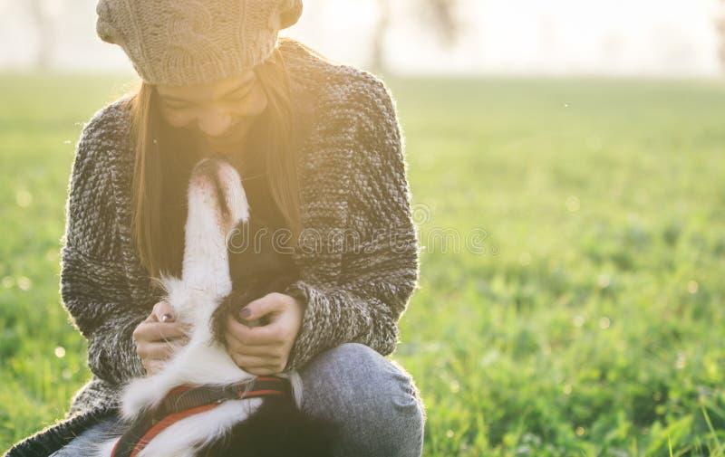 Mujer joven que juega con su perro del border collie imagen de archivo
