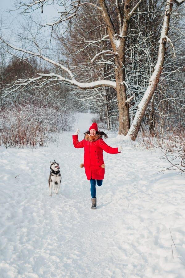 Mujer joven que juega con su perro fornido en parque del invierno fotografía de archivo libre de regalías