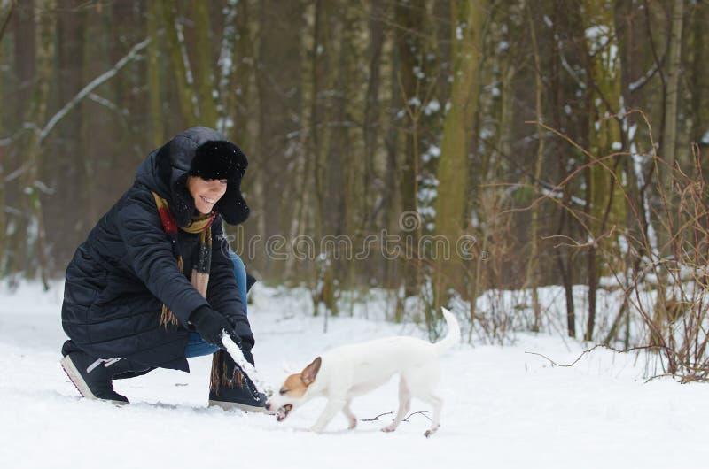 Mujer joven que juega con un perro fotos de archivo