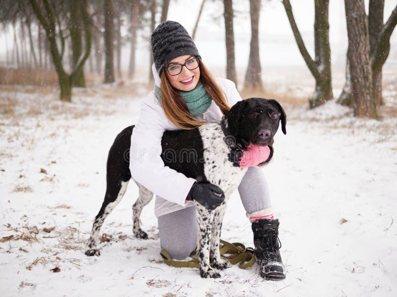Mujer joven que juega el invierno de la nieve al aire libre que abraza el perro ciego adoptado lindo del organismo Amabilidad y c foto de archivo libre de regalías