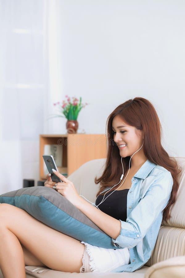 Mujer joven que juega el teléfono elegante que miente en sofá fotografía de archivo libre de regalías