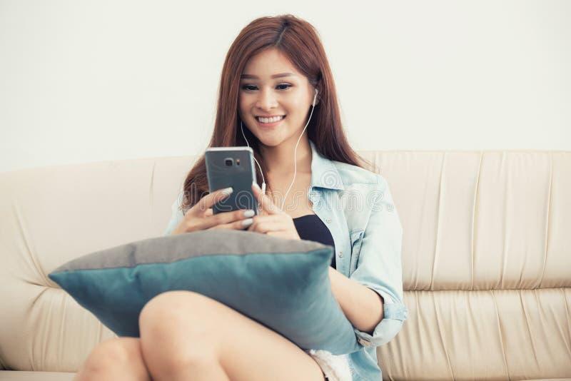 Mujer joven que juega el teléfono elegante que miente en sofá imagen de archivo libre de regalías