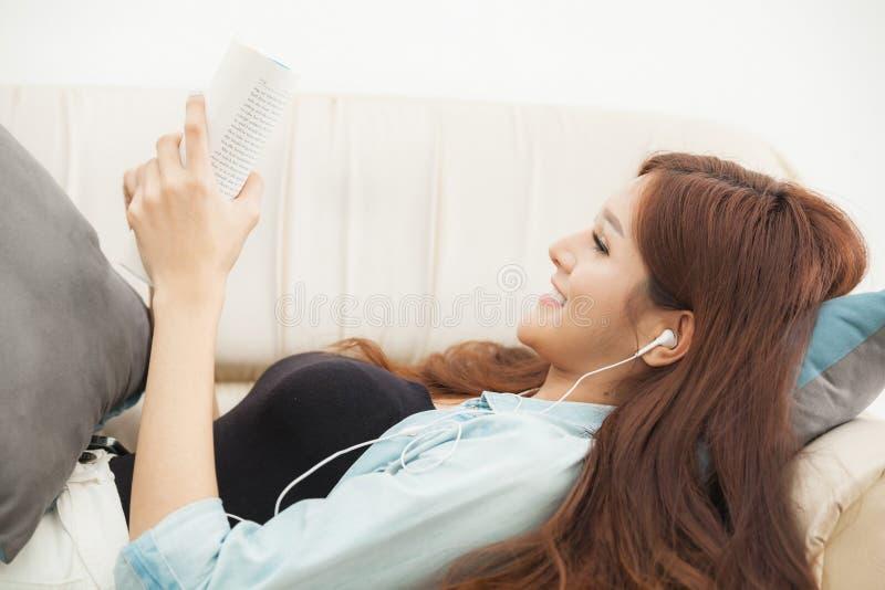 Mujer joven que juega el teléfono elegante que miente en sofá imágenes de archivo libres de regalías