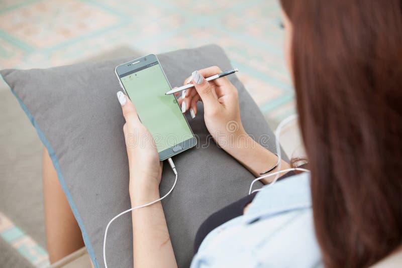 Mujer joven que juega el teléfono elegante que miente en sofá imagen de archivo