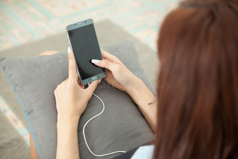 Mujer joven que juega el teléfono elegante que miente en sofá fotografía de archivo
