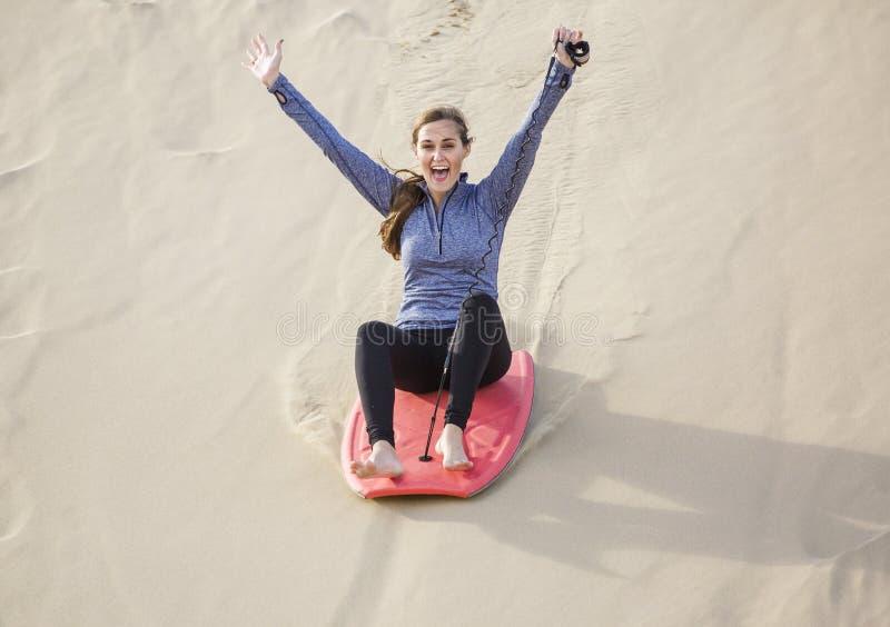 Mujer joven que juega en la forma de vida al aire libre de las dunas de arena imágenes de archivo libres de regalías