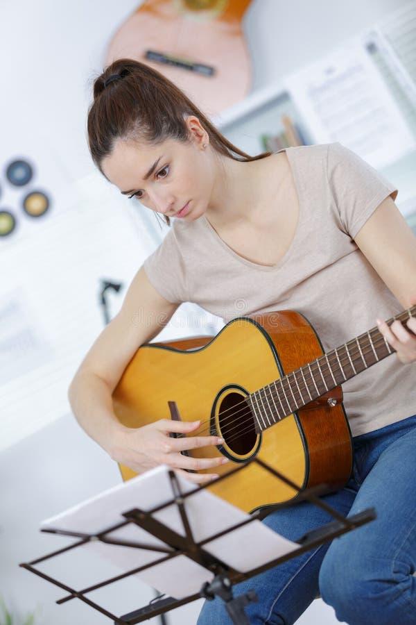 Mujer joven que juega en la guitarra acústica imagen de archivo