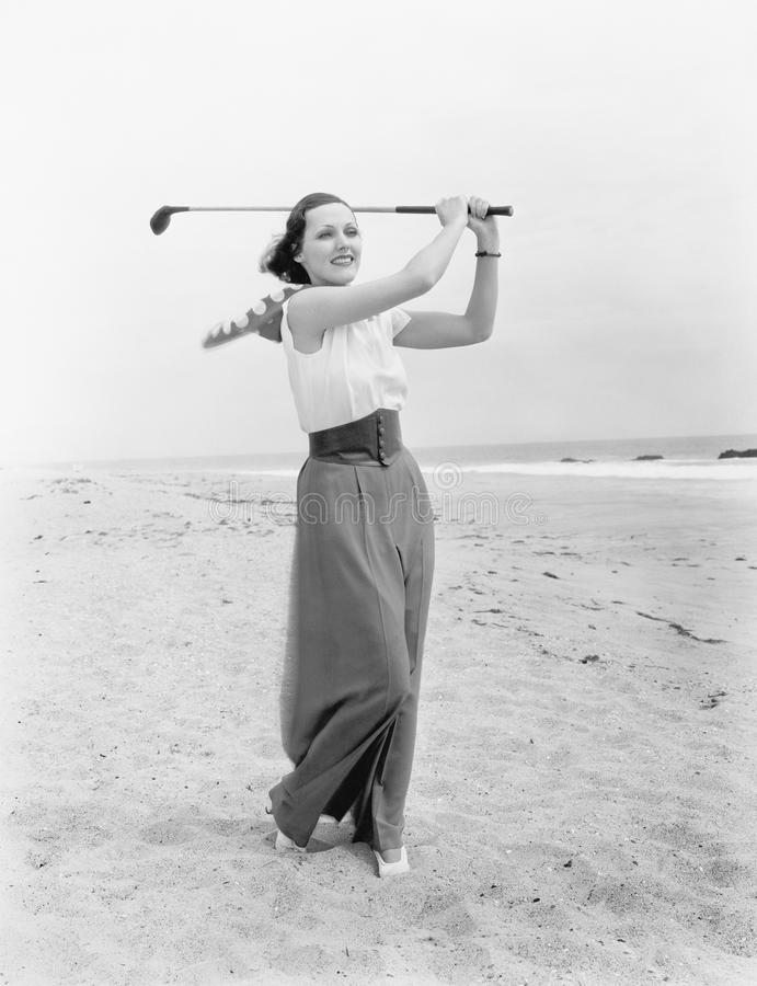 Mujer joven que juega a golf en la playa (todas las personas representadas no son vivas más largo y ningún estado existe Garantía imagen de archivo libre de regalías