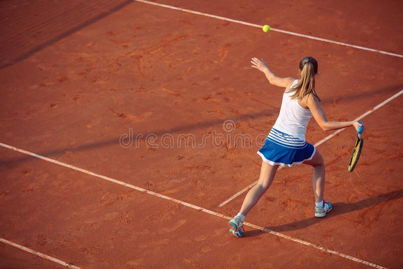 Mujer joven que juega a tenis en la arcilla forehand fotos de archivo libres de regalías