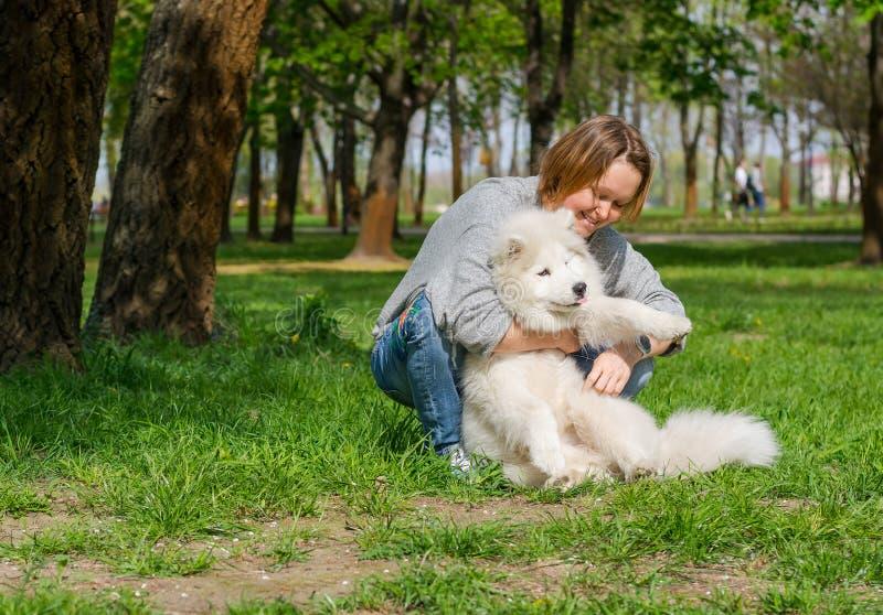 Mujer joven que juega y que abraza el perro mullido blanco del samoyedo y que ríe en un parque en la hierba imagen de archivo libre de regalías