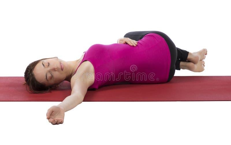 Mujer joven que la estira detrás durante yoga fotos de archivo