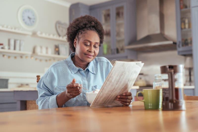 Mujer joven que lee el periódico mientras que come el desayuno en casa imagen de archivo