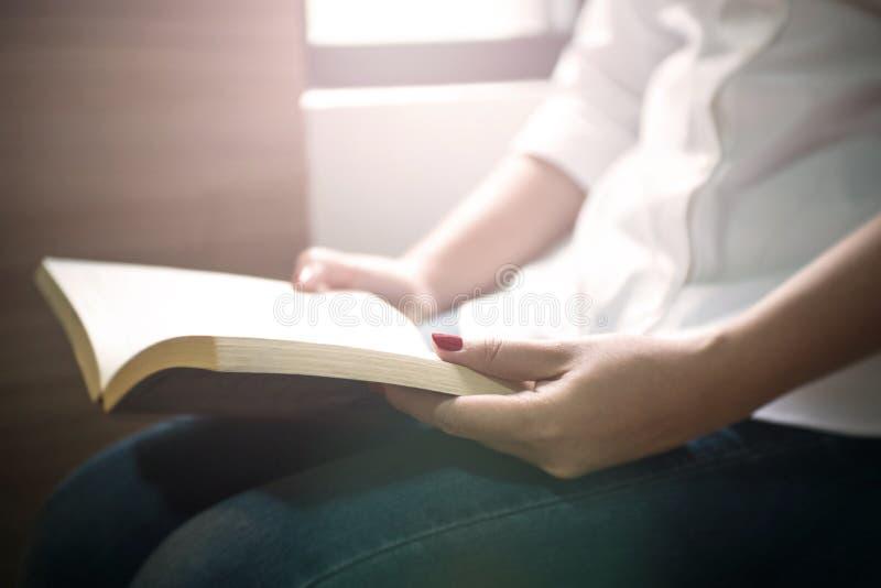 Mujer joven que lee un libro cerca de la ventana en la biblioteca imagen de archivo libre de regalías