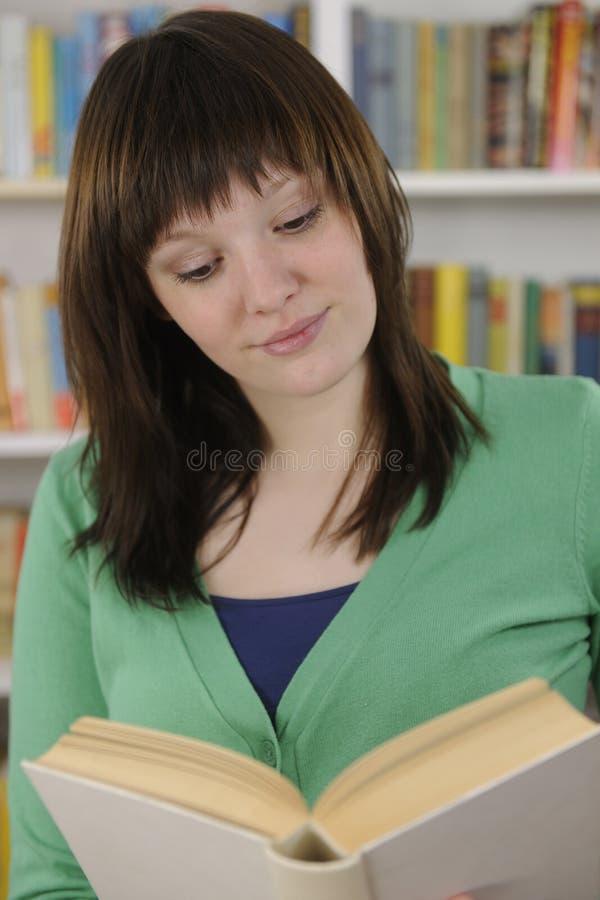 Mujer joven que lee un libro en biblioteca foto de archivo libre de regalías