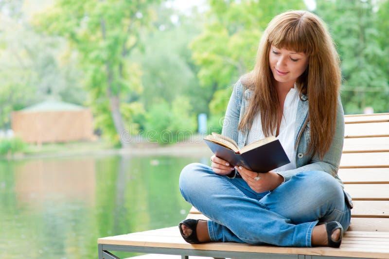 Mujer joven que lee un libro que se sienta en el banco foto de archivo