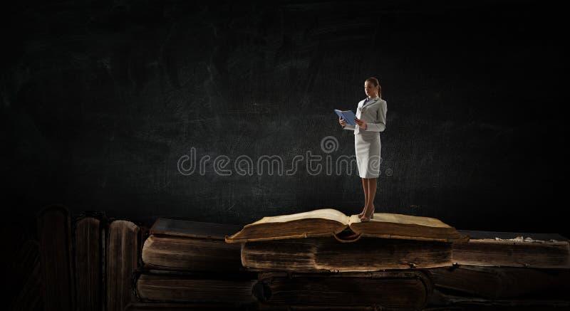 Mujer joven que lee un libro T?cnicas mixtas foto de archivo