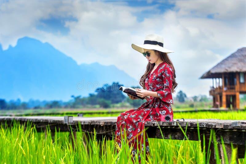 Mujer joven que lee un libro y que se sienta en la trayectoria de madera con el campo verde del arroz en Vang Vieng, Laos foto de archivo