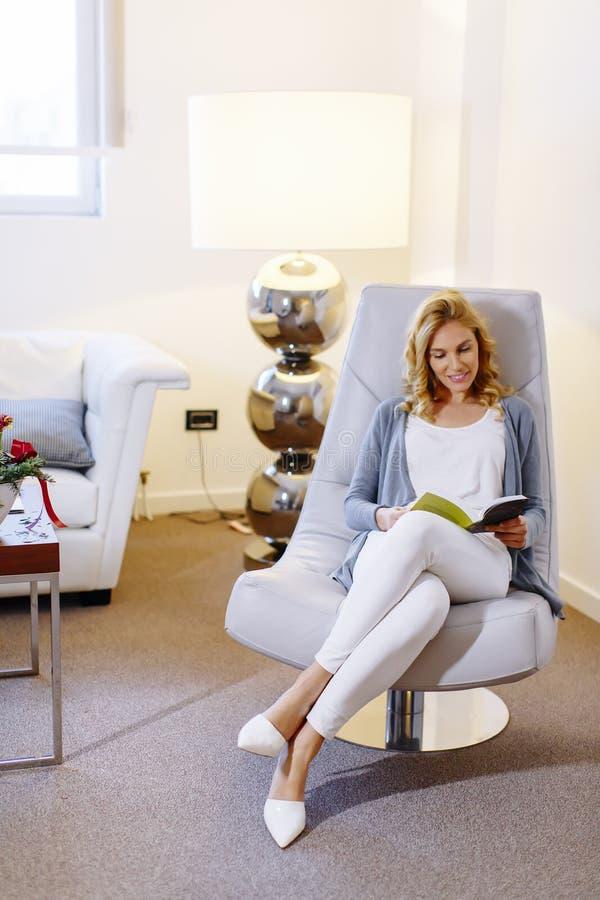 Mujer joven que lee un libro y que se sienta en silla cómoda en h fotografía de archivo libre de regalías