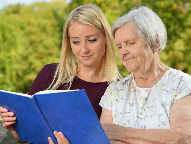 Mujer joven que lee a una mujer de los ancianos del libro fotos de archivo