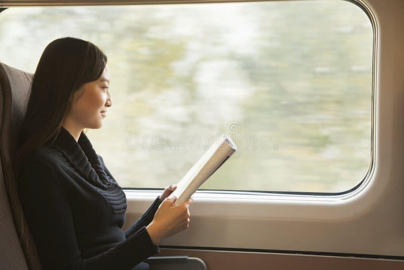 Mujer joven que lee una revista mientras que monta el tren fotografía de archivo libre de regalías