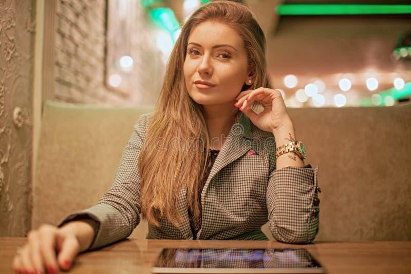 Mujer joven que lee una tableta digital fotografía de archivo