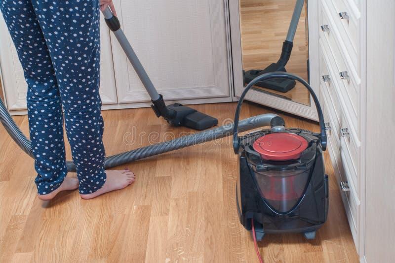 mujer joven que limpia la casa con la aspiradora con el aspirador Concepto de la economía doméstica fotos de archivo libres de regalías