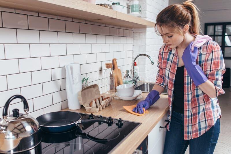 Mujer joven que limpia la tabla en la cocina imagenes de archivo