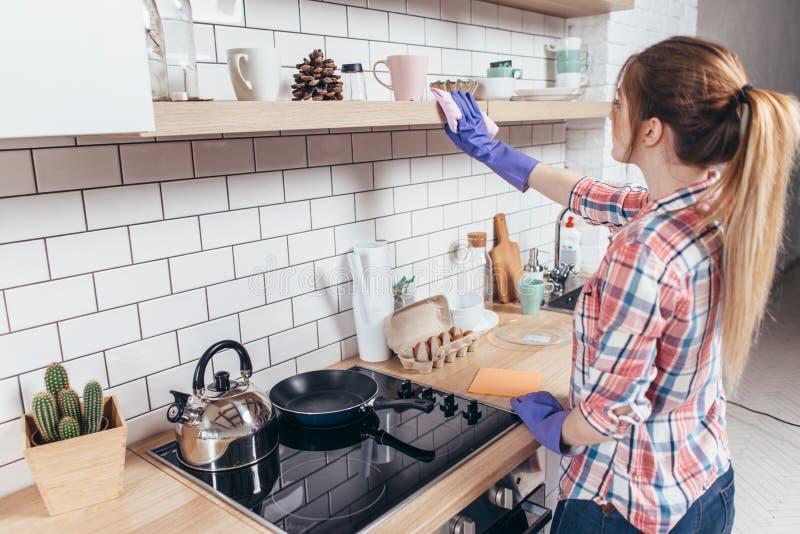 Mujer joven que limpia los muebles en la cocina imágenes de archivo libres de regalías